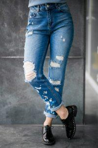 chica de medio cuerpo se ve los jeans azules desgastados
